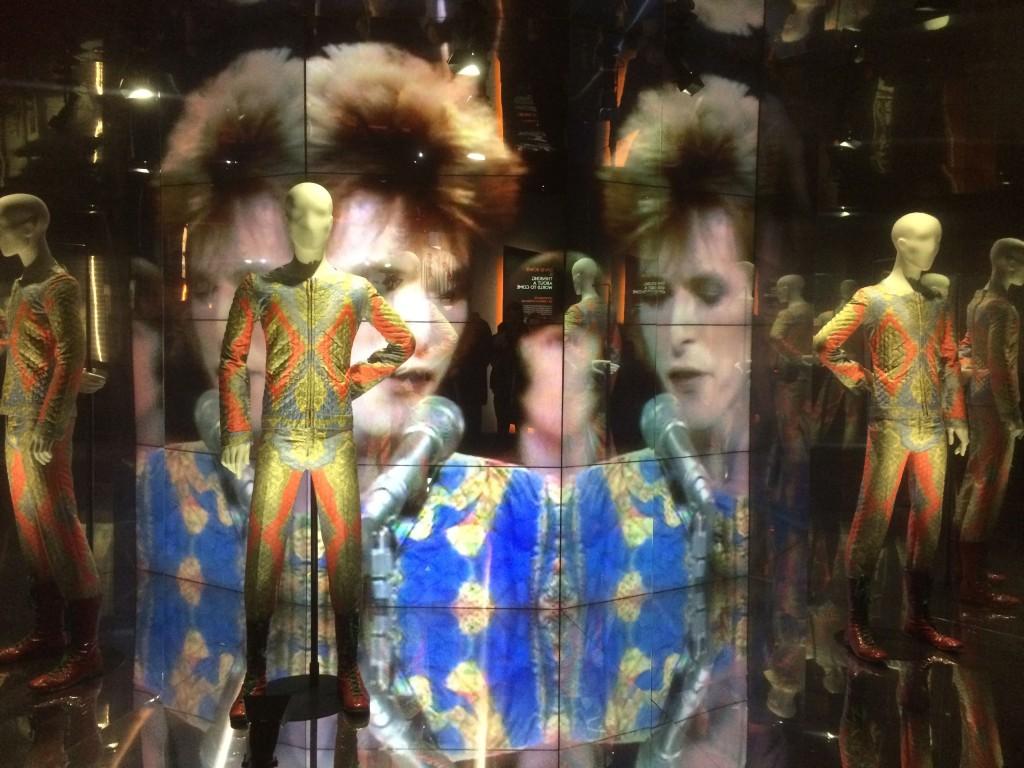 """L'une des vitrines """"kaléidoscopes"""" de l'exposition, mettant en scène costumes, vidéos et musiques de David Bowie"""